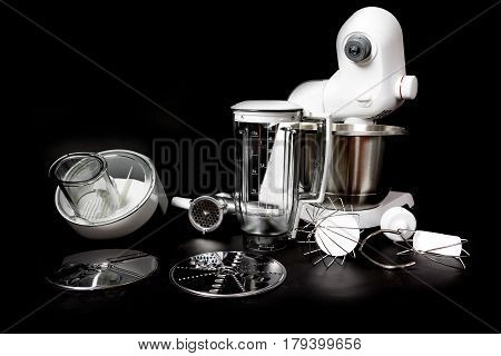 Kitchen robot with complete equipment closeup. All is on the black background. All potential trademarks are removed.