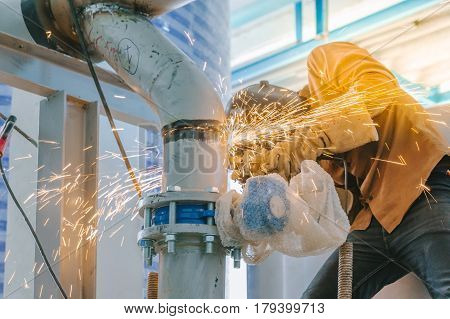 Heavy industry worker grinding steel pipe with wear protective mask by electric wheel grinding in construction site.