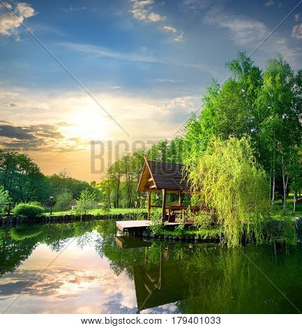 Arbour in birches near the pond at sunset