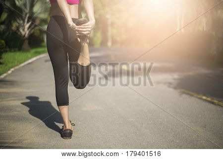 Close Up Of Legs And Torso Of Women. Young Woman Doing Warming Up Before The Morning Run.