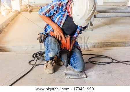 Construction worker using electric drill to install steel plate in a construction site.