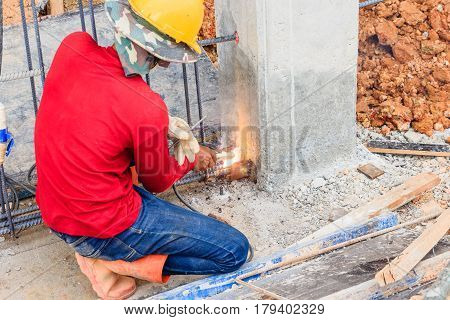 worker in protective glasses welding concrete reinforcing metal rods at construction building site