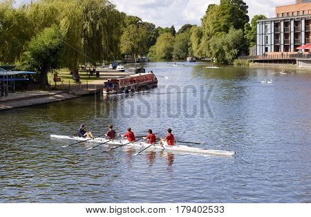 Stratford-upon-Avon Warwickshire England - August 18 2014 : Rowing team on the River Avon in Stratford upon Avon