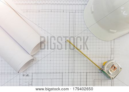 Workplace of architect - Architectural project blueprints blueprint rolls pen and measuring tape on plans. Engineering tools and gadgets view from the top. Construction background.