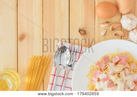 Spaghetti carbonara with chopped bacon cheese sauce and checkered towel on white dish over wooden table background Top view with copy space and text.