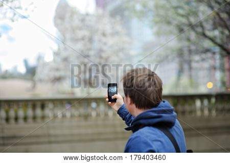 Middle age male tourist taking mobile photo using his smart phone