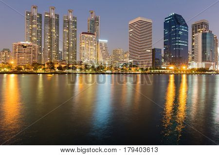 City office building nigh light with reflection cityscape background