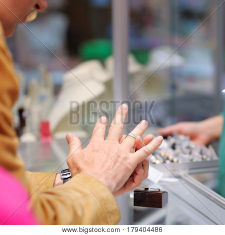 Man Trying Wedding Rings At A Jeweller