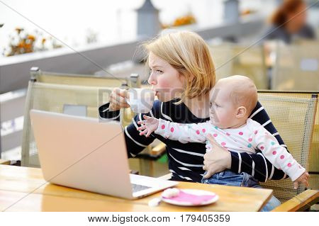 Tired Young Mother Holding 6-month Daughter And Drinking Coffee