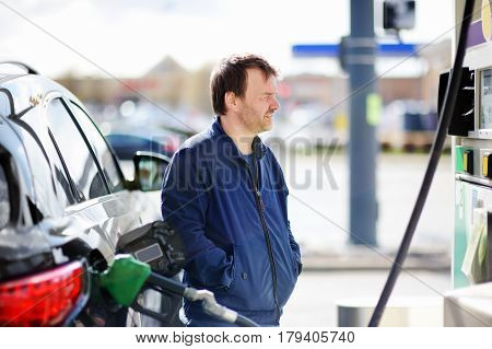 Portrait of Man filling gasoline fuel in car
