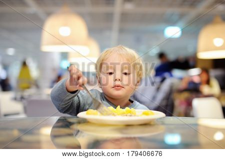 Toddler Boy Eating In Indoors Cafe