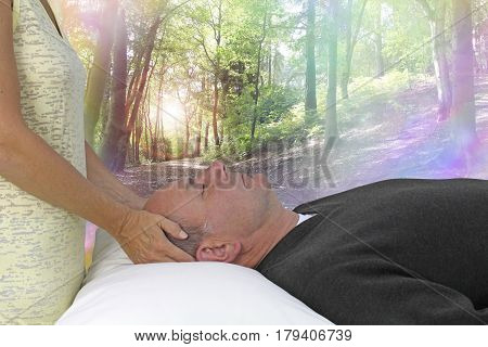 Dream State Spiritual healing session - female hands laid gentle either side of a male patient's head channeling healing energy with a beautiful woodland rainbow bokeh scene background