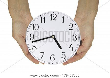 Nearly time to go home - female hands holding a clock face showing seventeen minutes to five, which is almost home time for many workers, isolated on a white background
