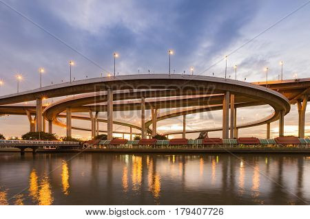 Twilight sky over round highway intersection overpass river front