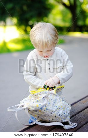 Toddler Boy Putting Toys In Backpack