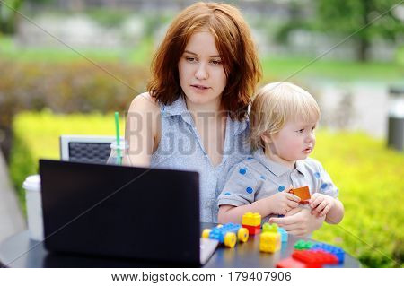 Young mother working oh her laptop and holding her sad toddler son