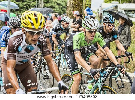 Saint Remy de Provence France - July 20 2014: The peloton rides on a wet slippery road curve in Saint Remy de Provence during the stage 15 of Le Tour de France 2014.