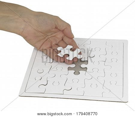 The last piece of the Jigsaw - Female hand holding a piece of jigsaw in one hand against a white jigsaw puzzle showing a space for the last piece on a white background