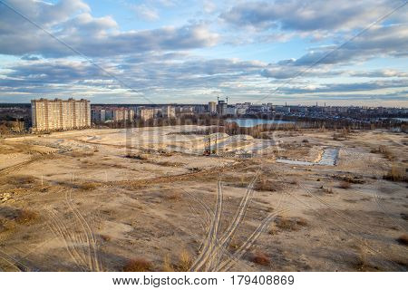 View from the roof to the wasteland - the site of future construction, a water reservoir and modern houses, Voronezh, Russia