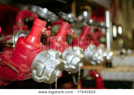 Fireman fire truck hose faucets in a row red and silver