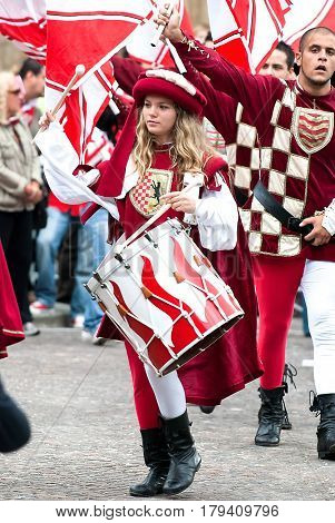 Asti, Italy - September 19, 2010: the historic Medieval parade of the Palio of Asti in Piedmont, Italy. Young Girl Drummer in medieval reenactment costumes