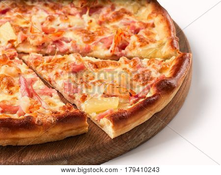 Close up view on piece of pizza with ham and pineapple on wooden cutting board. Isolated on white with clipping path