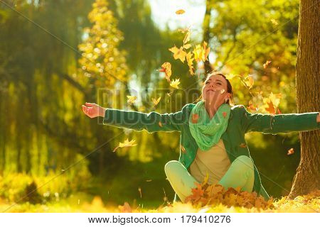 Happy Woman Throwing Autumn Leaves In Park