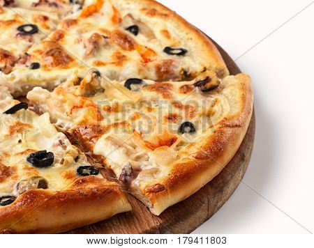 Close up view on piece of pizza with shrimp on wooden cutting board. Isolated on white with clipping path