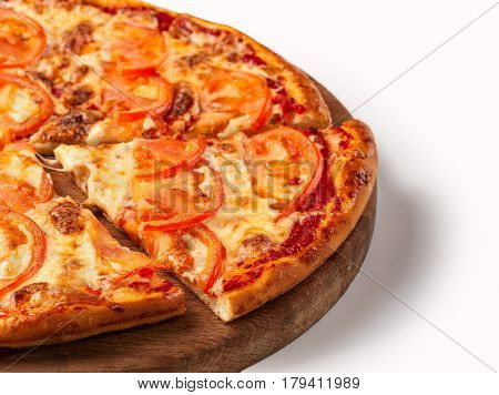 Close up view on piece of pizza with tomato and cheese on wooden cutting board. Isolated on white with clipping path