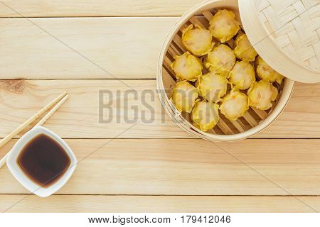 Steamed dumplings (chinese dim sum) in bamboo basket serve with chopsticks on wooden table background. Top view with copy space and text.