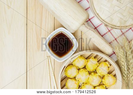 Steamed dumplings (chinese dim sum) in bamboo basket on wooden table background serve with chopsticks and napkin on a white background. Top view with copy space and text.
