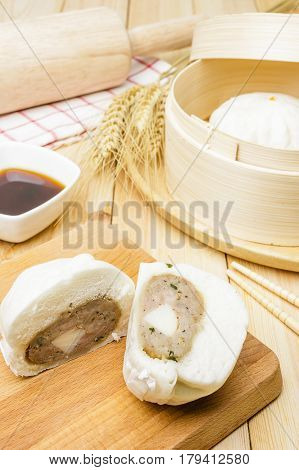 Steamed pork buns (chinese dim sum) in bamboo basket serve with chopsticks and napkin on wooden background Closed up