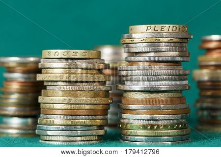 Coins stacked in several stacks can be seen against the background of green fabric