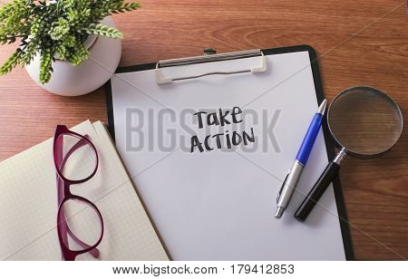 Take Action Word On Paper With Glass Ballpen And Green Plant.