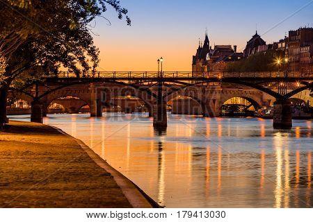 Sunrise on the Seine River banks Pont des Arts and Pont Neuf in the 1st Arrondissement of Ile de la Cite Paris France