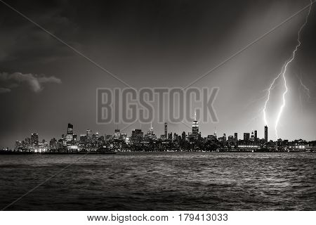 Lightning striking a New York City skyscraper at twilight (Black & White). Thunderstorm over Midtown West Manhattan from the Hudson River