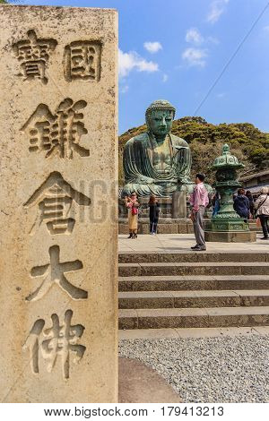 KAMAKURA, JAPAN - APRIL 14, 2014: Scenery of the Great Amida Buddha and tourists in Kamakura. Kamakura Daibutsu is the famous landmark located at the Kotoku-in temple in Kanagawa Prefecture.