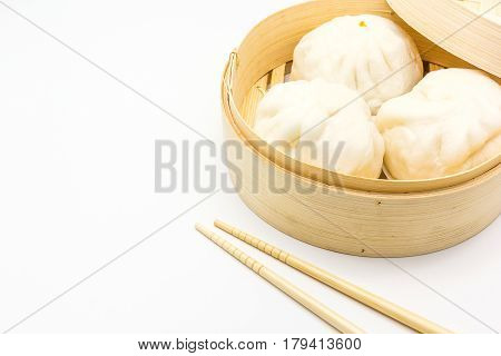 Steamed pork buns (chinese dim sum) in bamboo basket serve with chopsticks on a white background Top view with copy space and text.