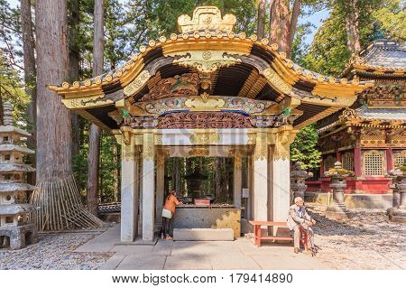 NIKKO JAPAN - APRIL 16 2014: A shinto priest sweeps under the Yomeimon gate on April 16 2014 in Nikko JP. Founded in 1617 the remains of the first shogun Tokugawa Ieyasu are entombed here.