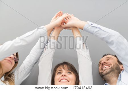 Group of business people enjoying and celebrating the success of team work. They consist hands upward in a gesture of victory.