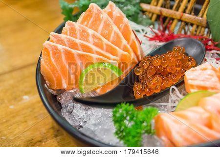 Salmon sashimi set with Salmon and Salmon caviar on big sashimi plate (Japanese food). Delicious Japanese sashimi sushi set or platter. Raw fresh Salmon meat sashimi