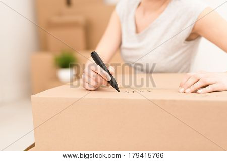 Young woman signs a box while moving. Cleaning and packing. The concept of move.