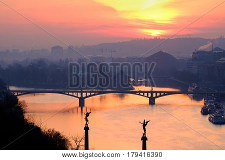 Scenic View Of Sunrise Over The River And One Of Prague's Bridges