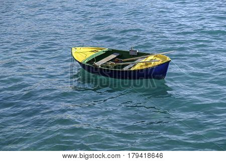 Small colorful row boat and oars moored in the clear blue water of the Atlantic Ocean with reflection on the waves and ripples.