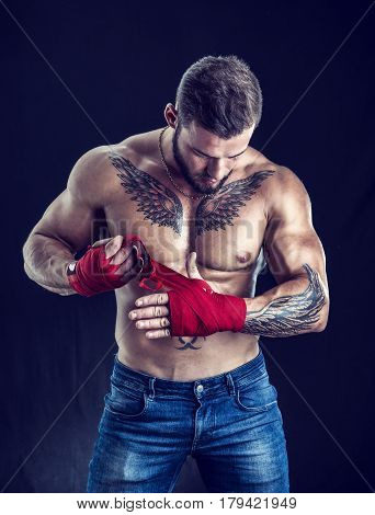 Muscular handsome topless boxer man preparing red gloves, looking down, in studio shot against black background