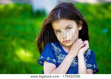 Portrait of beautiful little girl in summer park
