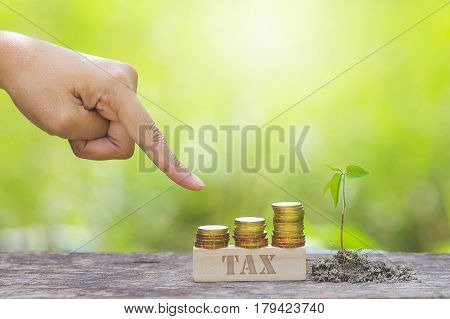 TAX WORD WITH BUSINESSMAN HAND POINTING TO STACK OF GOLD COIN