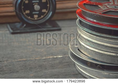 A stack of old bobbins with films and a black timer stand on a wooden table