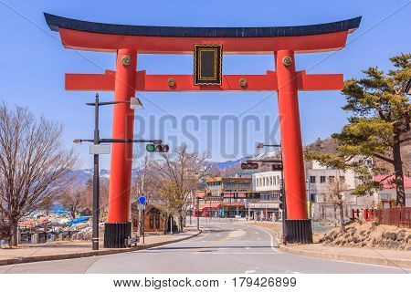 NIKKO JAPAN - APRIL 14 2014: Massive torii gate of Futarasan Shrine at the front of lake Chuzenji in NIkko