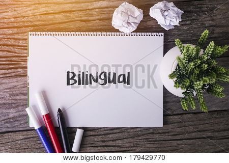 Bilingual Word With Notepad And Green Plant On Wooden Background.